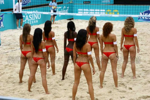 Some beautiful bikini cheerleaders doing their routine to get the crowd excited during a volleyball match.
