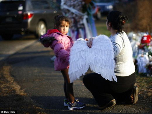A girl and a woman place angel wings at the Sandy Hook Elementary School sign in Newtown