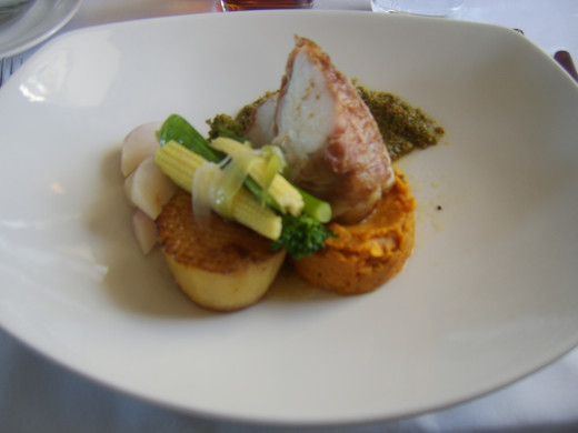 Bacon wrapped monkfish tail with fondant potato and assorted vegetables