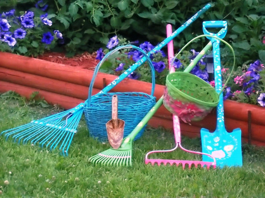 Add beauty to your landscape with this colorful and easy garden project. Image shows lawn and garden rakes, shovel, trowel, baskets in colors of pink, blue, and green.