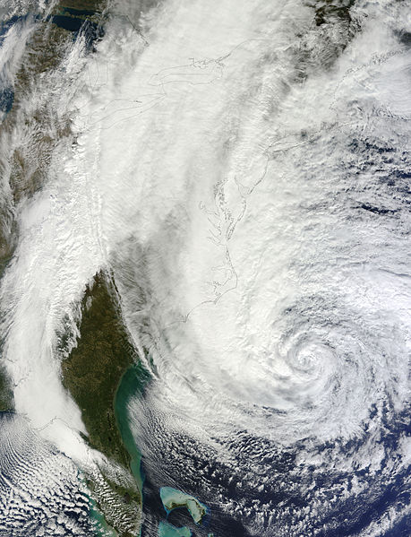 """""""A satellite image of the storm on October 29, with most of the U.S. coastline artificially highlighted. The entire east coast is visible, with a cloudless Florida coast seen at the bottom of the image and the outline of the coast of Maine at the top"""