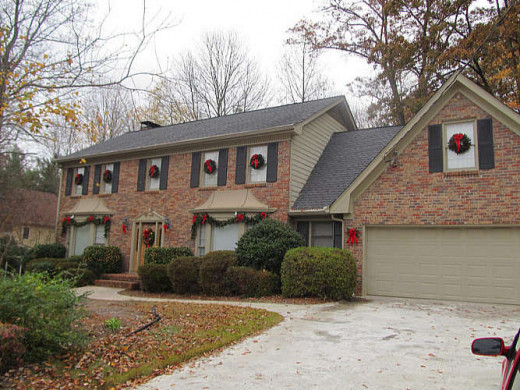 Classic Colonial Two Story with Evergreen Holiday Wreath on the Window