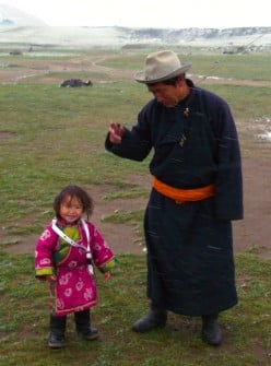 A nomad father and child weathering an early season blizzard at Orkhon waterfall