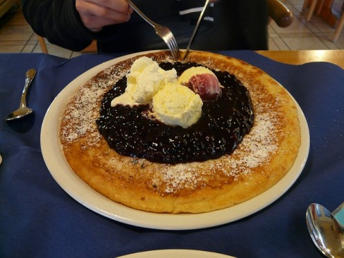 Large pancake dusted with powdered sugar, topped with cranberries and vamilla ice cream.