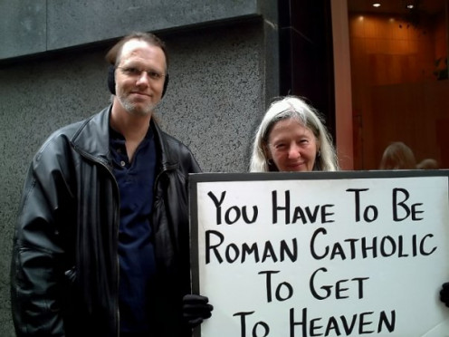 """Christmas in New York City, December 2006. Delusion comes in many shapes and sizes, and yet, we can all still be friendly with each other! This nice lady agreed to pose with me, holding up her """"truth""""-filled sign."""