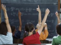Children raises hands in classroom