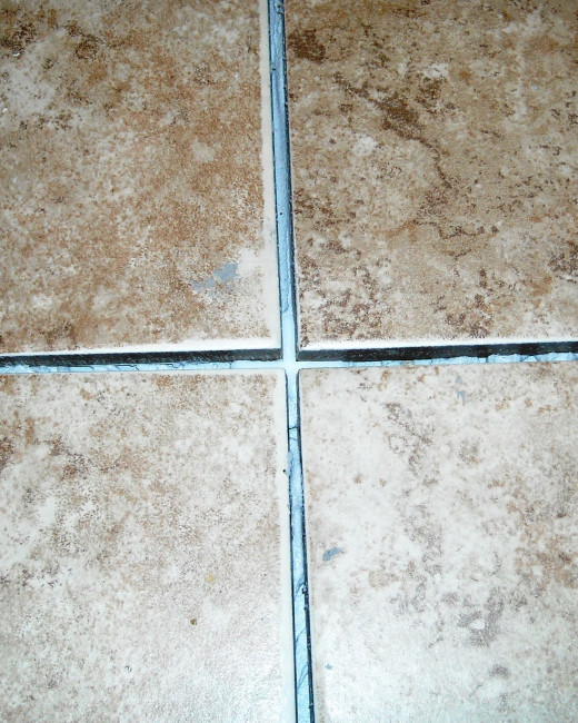 A tile spacer pushed down into the adhesive at a corner to keep the tiles square.