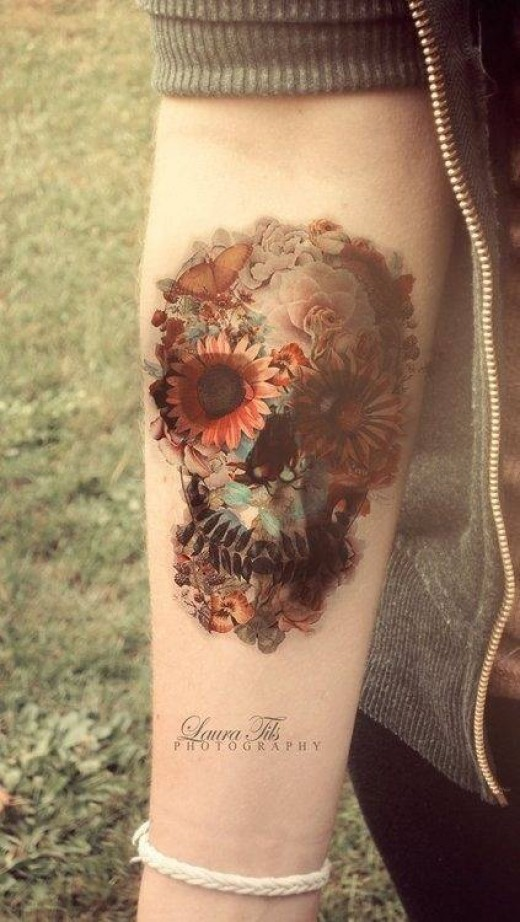 Skull tattoo with flowers on forearm
