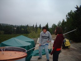 I demonstrate pigeage to a friend in an open air vinification (before I had built the winery)