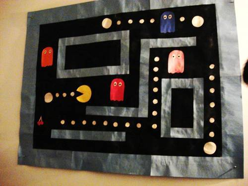 an example of a poster made by me of a pacman scene. made from wrapping paper, spray paint, and construction paper. over 4 feet in width.