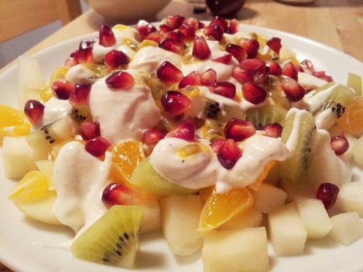 A fruit salad topped with Greek yogurt.