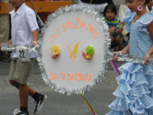Children in cultural costumes carry a sign during the Old Spanish Days Children's Parade on Saturday August 4, 2013.