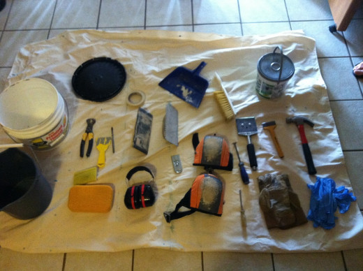 Tile working tools and gear laid out on a drop cloth.