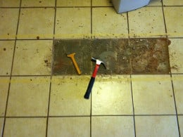 Busting out the tile with a mason's chisel and a hammer.
