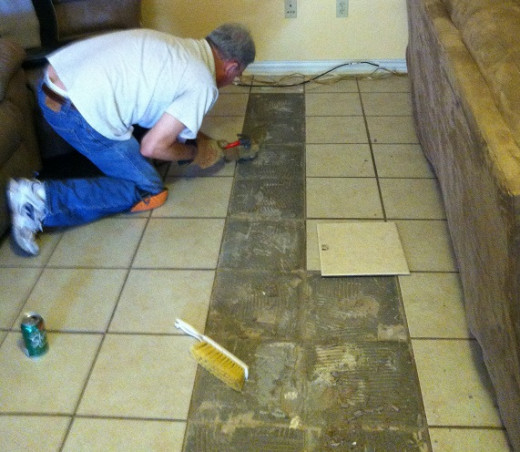 Chipping away the grout on the sides to make room for the new tile.