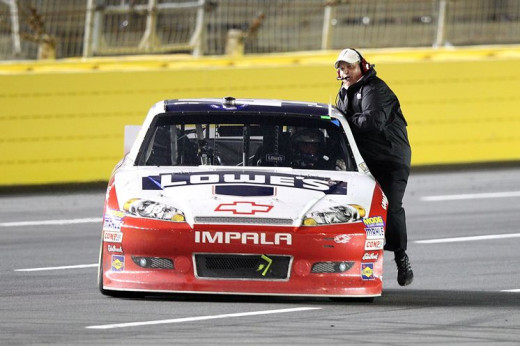 Rick Hendrick rides on Jimmie Johnson's window ledge after another Johnson victory