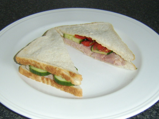 Simple ham, cucumber and tomato sandwich is served