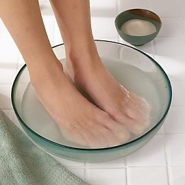 Soak feet to begin to give yourself a pedicure.