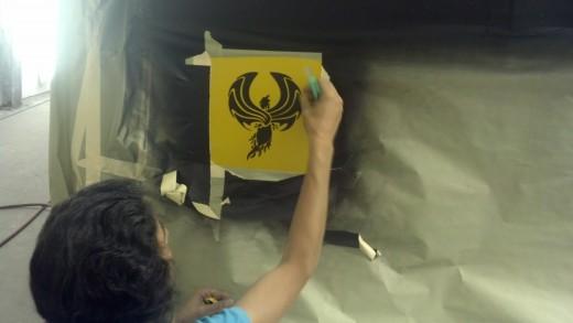 Michele installing the trademark 'Phoenix' of Phoenix Commercial Paint Inc