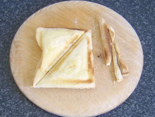 Cooked toastie is trimmed for serving