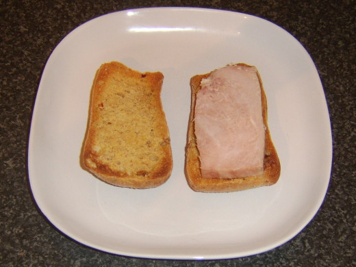 Slice of ham is laid on bottom half of ciabatta