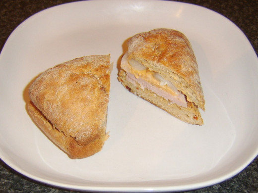 Ham, spicy cheese and pickled onion ciabatta is sliced and served