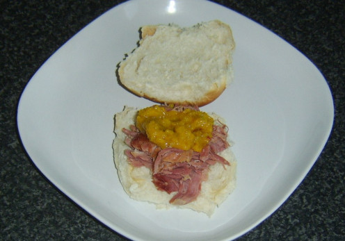Warm, shredded roast ham on a bread roll with piccalilli