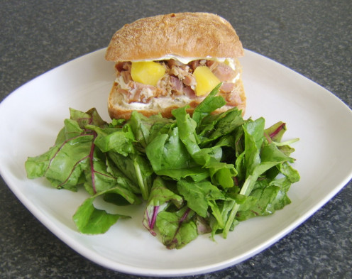Ham, cream cheese and pineapple are served in a pain rustica bread roll with a green leafed salad