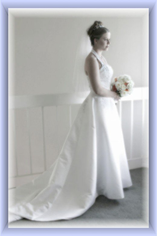 A modern bride wearing many of the traditional items - white dress, veil, flowers and tiara.