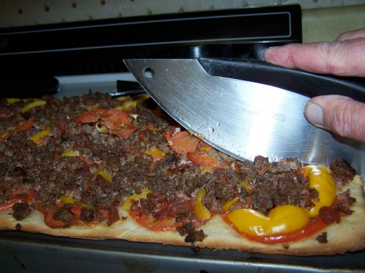 The pizza being sliced.