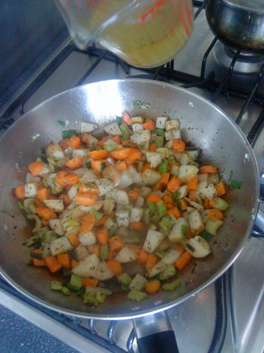 Adding stock to vegetable mix.