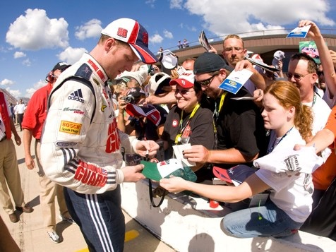Dale Earnhardt Jr. signing autographs for fans on pit lane before a race