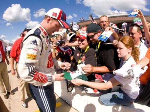 Dale Earnhardt Jr. signing autographs for fans on pit lane before a race