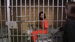 Female Prisoner shackled in a jail cell