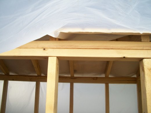 The plastic remains under the roof sections to divert any water leaks to the outside face of the wall siding.