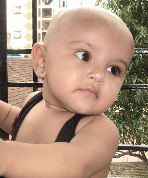 A bald kid in window