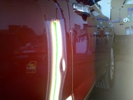 The light allows the repairer to see the shape of the ding, and using that light they will work the metal to remove the dent leaving a smooth surface.