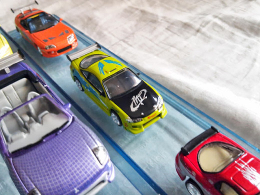Assorted Fast and Furious diecast cars. The green one is the import Mitsubishi Eclipse used by Brian on the first film. The red one in front is the Mazda RX7 used by Dom.