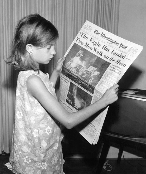 People collect newspapers with famous headlines.