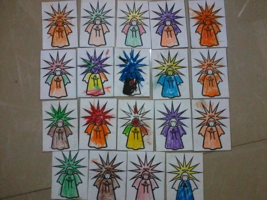 """During a random Saturday visit in a poor community in Manila, children took time coloring their """"angels"""" and wrote their names at the back of the cards. Besides coloring time, they were also shown a book while storytelling."""
