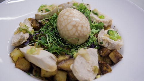 """Year of the Dragon Hash"" - Diced potatoes, chili-vinegar-soy sauce, white chicken mat, ginger-scallion sauce, cress, sprouts, and a tea egg."