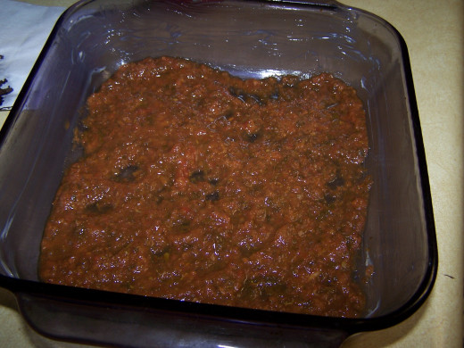 I start by spreading a layer of tomato sauce to the bottom of the baking dish.