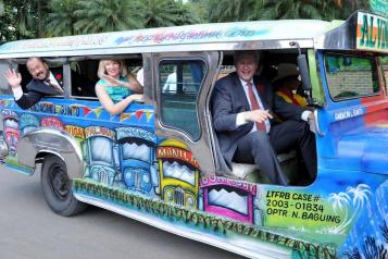 Canadian Prime Minister Stephen Harper (R), his wife Laureen (C), and Canadian Senator Tobias Enverga (L) ride a jeepney during their visit to Fort Santiago in Manila.