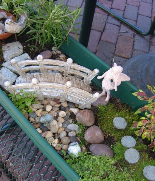 I made a small stream with pebbles that travel under this bridge. Notice there is  a ceramic teapot and a small frog.  I Know there is a Dragon Tear in there, but i can't find it in this photo. Perhaps you can.