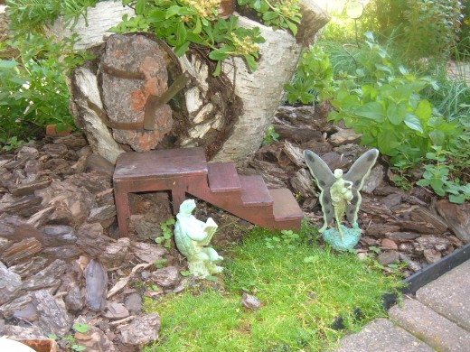 A friend made these steps for me to reach this door in a Birch tree stump. This garden hosts my herbs and a statue or two, plus a wagon with a large egg.