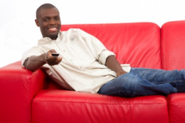 A guy sitting on a couch with a remote control