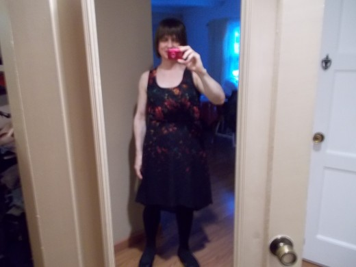 Emily in a pretty black dress with floral patterns