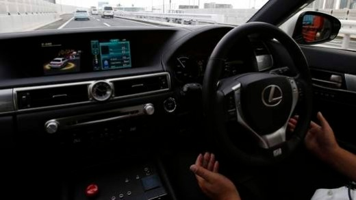 Driver with hands off the wheel. To the left is the auto-pilot controller display shown above