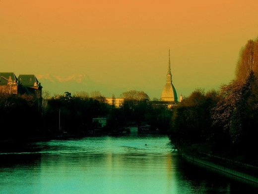 The high dome of the Mole Antonelliana viewed from the river at sunset. The Mole (1863-1889), which takes the name from its architect Alessandro Antonelli, is the tallest building in Turin (167,5 M) and the symbol of the city.