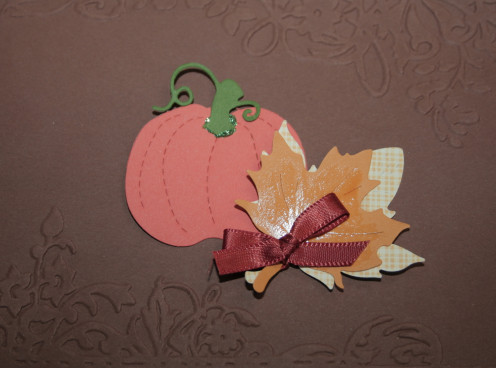 Pumpkin and leaf shapes adhered to embossed background.